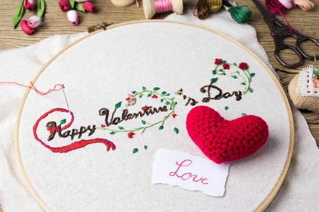 Valentine embroidery with love message and red heart on wood table