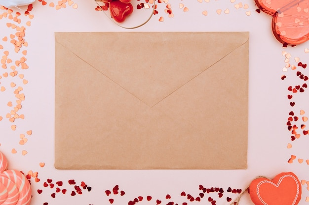 Valentine envelope on a pink background. in a circle there are caramel hearts, sweets, a wicker basket. space for text Premium Photo