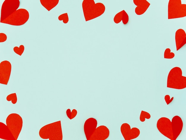 バレンタインフレームは、愛の概念のためのコピースペースでシアンの背景に赤いハート紙を作りました。