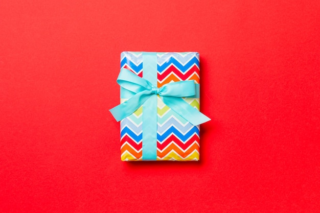 Valentine gift box on colored background, top view.