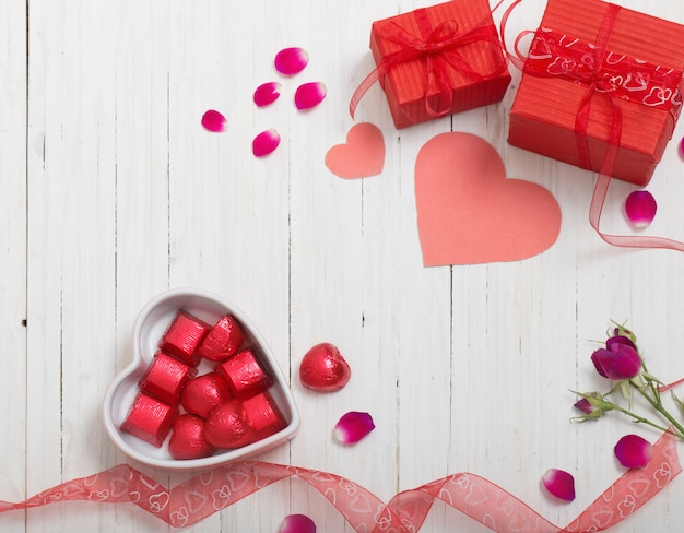 Valentine gift box and red heart shapes on white wooden board