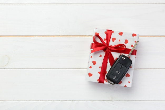 Valentine gift box with red ribbon and key car. flat lay