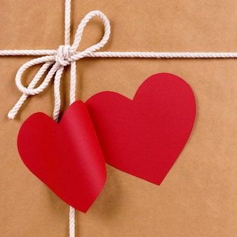 Valentine gift with red heart shape gift tag, brown paper package