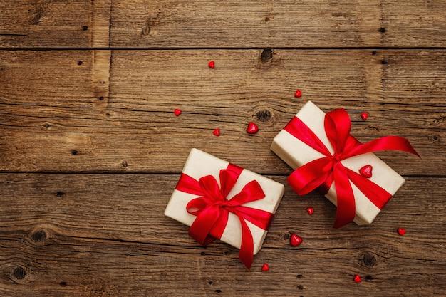 Предпосылка поздравительной открытки валентинки с подарочными коробками, красными лентами и разными сердцами. старинный деревянный стол. концепция свадьбы или дня рождения, место для текста, плоская планировка