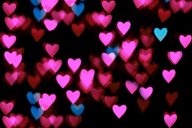 バレンタイングランジハート型ライトテーブル。黒のテーブルにハート型のバラと青のボケ味。