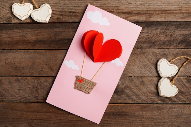 Valentine handmade card with red heart parachute on wooden table