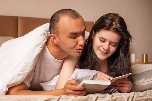 Valentine  happy couple lie on the bed and read a book