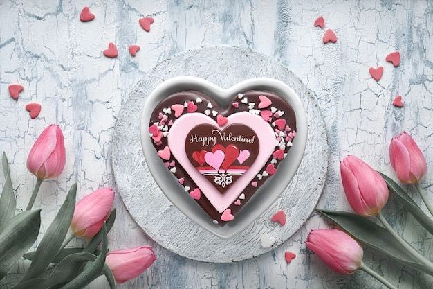 Valentine heart cake with chocolate, sugar decorations  and a bunch of pink tulips