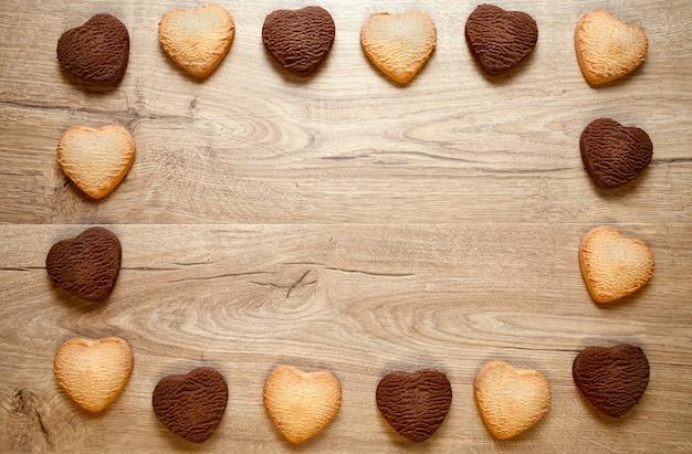 나무 배경에 발렌타인 하트 쿠키 프레임입니다. 구운 버터와 초콜릿 쿠키는 텍스트를 배치합니다. 플랫 레이