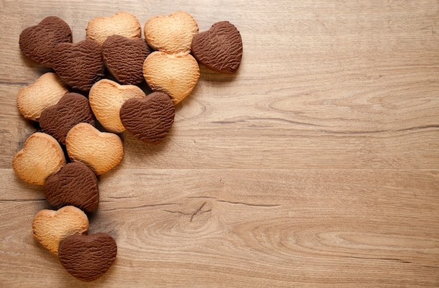 나무 배경에 발렌타인 하트 쿠키입니다. 구운 버터와 초콜릿 쿠키 및 텍스트 배치.