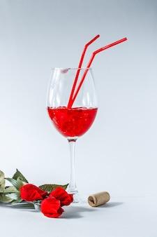 バレンタインハートの背景。バレンタインレッド。赤いハートとバレンタインデーの白い背景、上面図。グラスの中のハート、カクテル。ワインストッパー