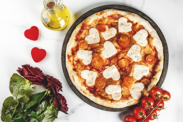 Valentine holiday food , pizza margarita with heart shaped cheese, white marble , copyspace top view, with roses