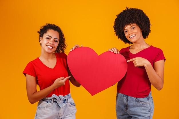 紙のハートを持ったバレンタイン レズビアン カップル。バレンタインデーのコンセプト