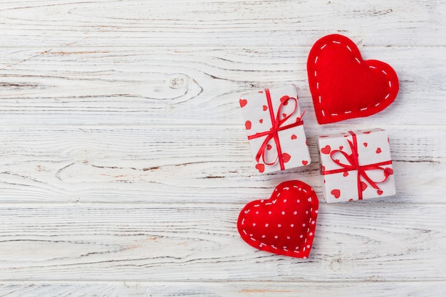 Valentine or other holiday handmade present in paper with red hearts and gifts box in holiday wrapper