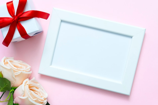 Valentine photo frame with sweet rose and gift box on pink background with copyspace for text.
