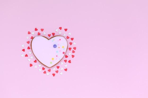 Валентина розовое печенье в форме сердца с маленькими красными и белыми сердечками в любви.