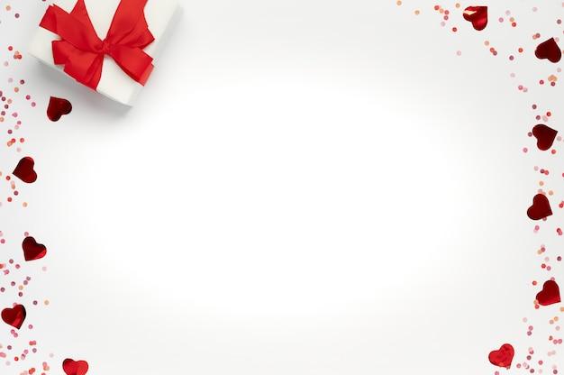 バレンタインポストカード。赤い弓と白い孤立した多くのキラキラハートのギフトボックス