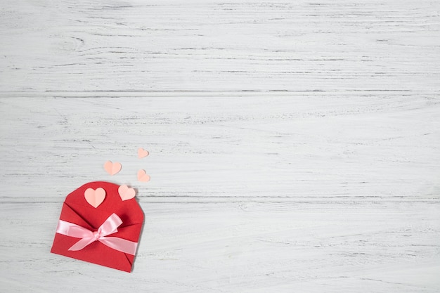 Valentine red envelope with pink hearts. valentines day card, love flat lay on white wooden background with copy space.