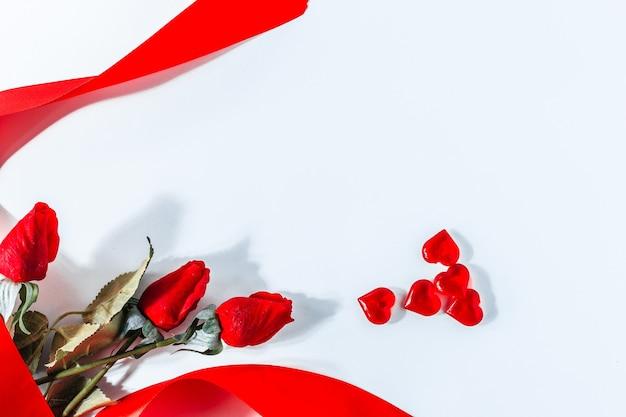 バレンタインローズ白い背景。バレンタインレッド。赤いバラとリボン、上面図とバレンタインデーの白い背景。