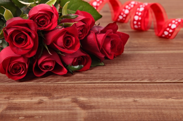 San valentino rose rosse e nastro su tavola di legno