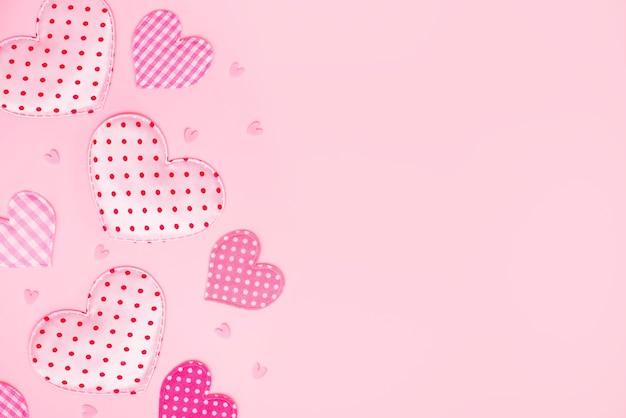 バレンタインの背景。コピースペースのあるパステルピンクに異なるパターンのファブリックハート。居心地の良い心の背景。ハート型のクッション。