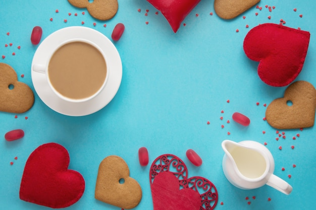 Valentine's card. cup of black coffee with milk, red heart, sweets on blue. top view.