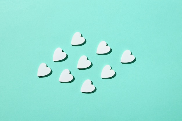Валентинка из бумажных сердечек ручной работы на пастельно-бирюзовой стене с жесткими тенями, копией пространства. поздравительная праздничная открытка.