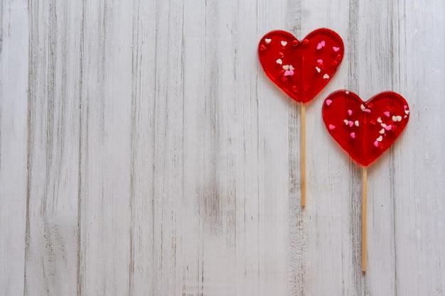 Валентинка. два леденца на палочке в виде сердца на деревянных фоне