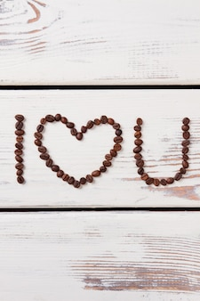Valentine's coffee. i love you. heart made of coffee beans on wooden surface.