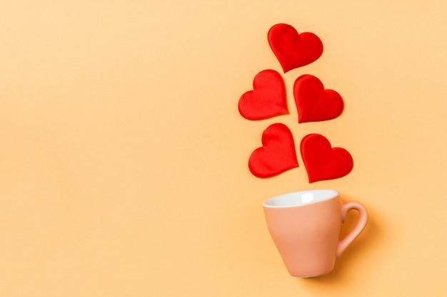 カップから落ちる赤いハートのバレンタインの組成