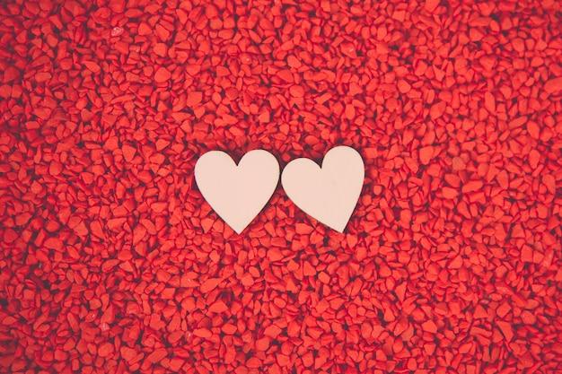 バレンタインデー、2月14日concetps。赤い砂の背景に2つのハートをクローズアップ。