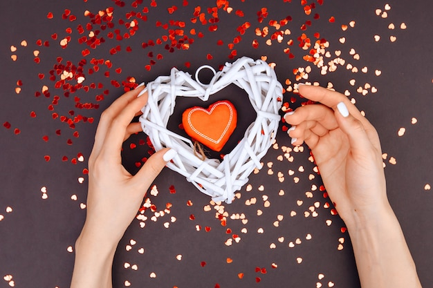 Valentine's day . the 14th of february. in the hands of the girl there are two hearts red and white. there are many small hearts in a circle.