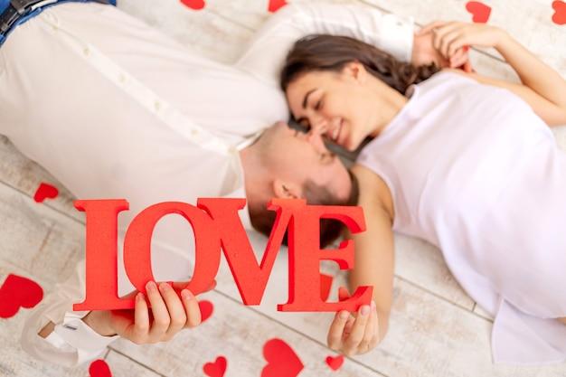 День святого валентина, влюбленная пара лежит среди сердечек на полу и держит большую надпись love
