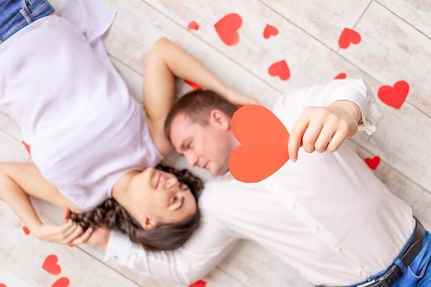 День святого валентина, влюбленная пара лежит среди сердец на полу, обнимая и держа большое красное сердце
