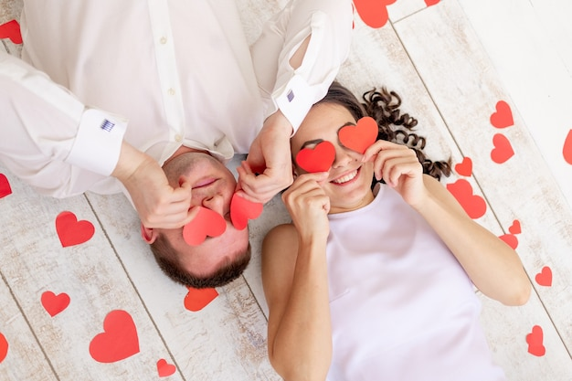 День святого валентина, влюбленная пара лежит среди сердец на полу с закрытыми сердечками глазами