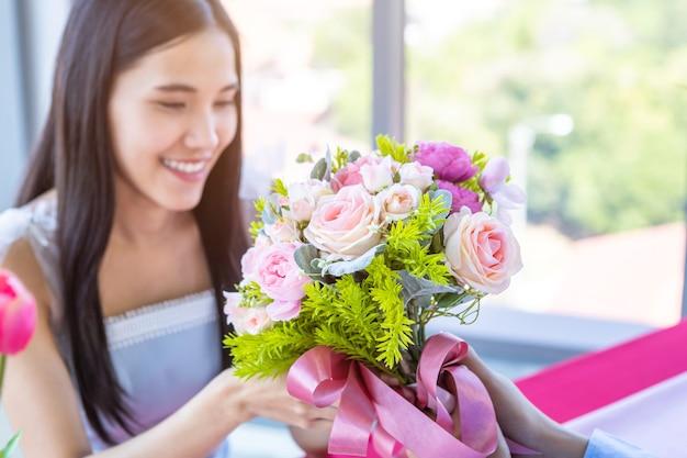 발렌타인 데이 및 아시아 젊은 행복한 커플 개념, 꽃다발 장미를 들고 있는 남자, 그녀의 얼굴에 미소를 짓고 있는 여성에게 손을 얹고 점심 식사 후 놀라움을 기다립니다 레스토랑 배경