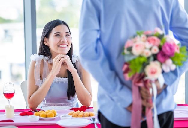 バレンタインデーとアジアの若い幸せなカップルのコンセプト、アジア人のクローズアップ彼女の顔に手でバラの女性の花束を持っている男性が昼食後の驚きを待っていますレストランの背景で