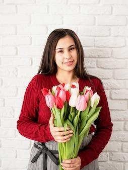 발렌타인 데이와 여성의 날. 중소기업. 신선한 다채로운 튤립 꽃다발을 들고 여자 꽃집