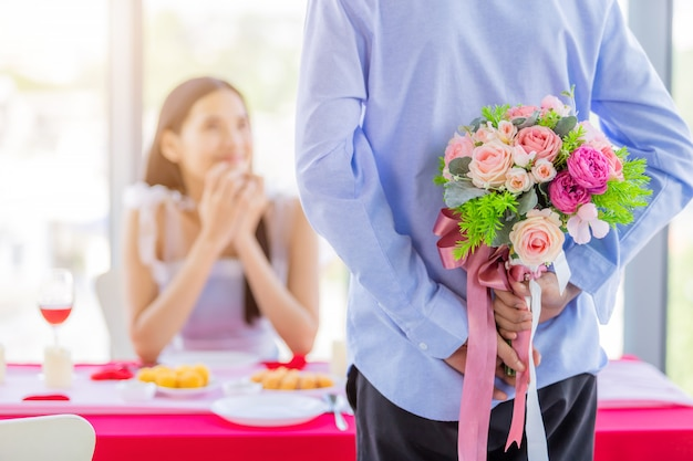 Valentine's day and asian young happy couple concept,close up of asian a man holding a bouquet of roses woman with hands over her face awaits surprise after lunch in a restaurant