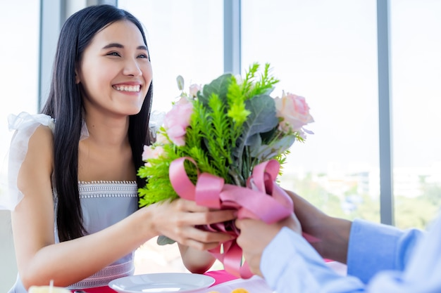 Valentine's day and asian young happy couple concept, a man holding a bouquet roses give to woman with hands over smiling her face awaits surprise after lunch in a restaurant