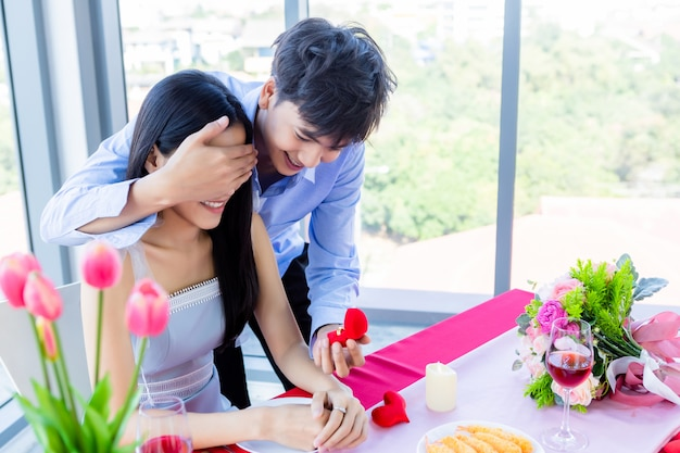 Valentine's day and asian young happy sweet couple concept,asian a man with engagement ring making proposal of marriage to woman after lunch in a restaurant , bride and groom wedding plans