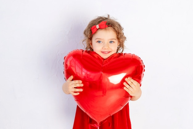 Valentine's day baby. a little girl in a red dress holds a large ball in the shape of a heart
