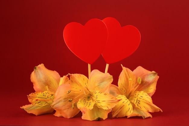 バレンタインデーの背景。赤い背景の花の赤いハートの構成。コピースペース