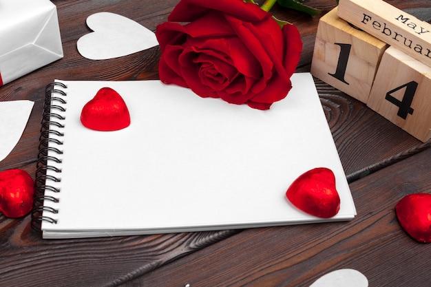 バレンタインデーの背景。空の空白のノートブック、ギフトボックス、白地に花、トップビュー。テキスト用の空き容量