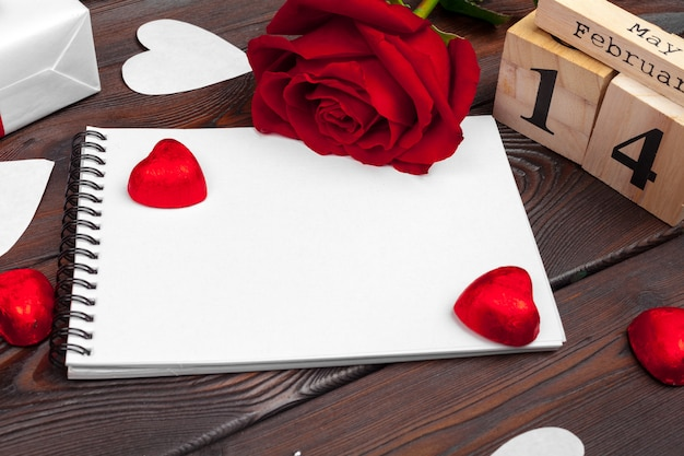 Valentine's day background. empty blank notebook, gift box, flowers on a white background, top view. free space for text