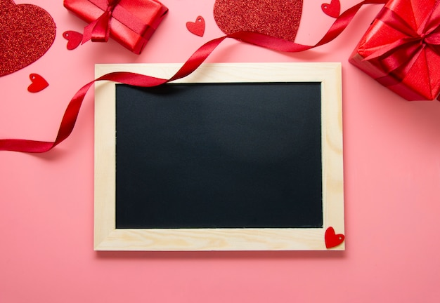 Valentine's day background. empty chalk board frame, hearts and red ribbon