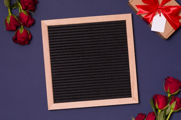 Valentine's day background, empty letter board with red roses and gift.