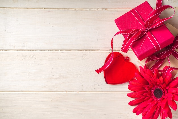 バレンタインデーの背景。明るい木製の背景にお祝いのリボン、ガラスの赤いハートと赤いガーベラの花のギフトボックス。テキスト用のコピースペース