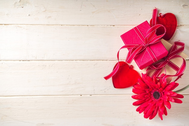 Valentine's day background. gift boxes with festive ribbon, glass red heart and red gerbera flower on light wooden background. copy space for your text
