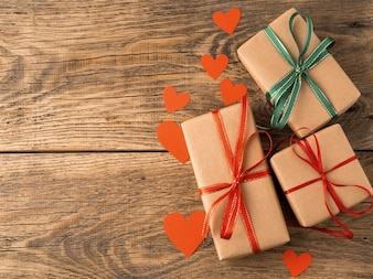 Valentine's day background. Gifts wrapped with Kraft brown paper, with red ribbons, hearts